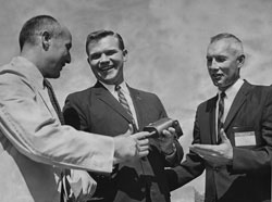 L. William Seidman, Gov. Swainson, and President Zumberge hold defective detonator.